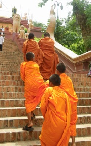 monks climbing the stairs at Wat Phnom, Phnom Penh, Cambodia